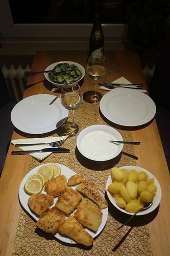 Panierte Filets vom Victoriasee-Barsch mit Joghurtdip, Salzkartoffeln und Gurkensalat (Tischbild)