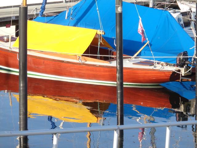 buntes Boot im Segelhafen gespiegelt