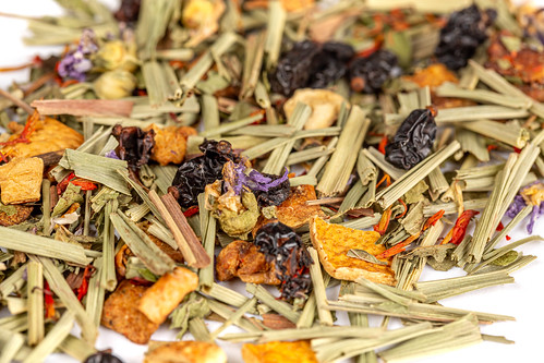 Background of dried tea with pieces of apple, orange, berries of barberry and saffron