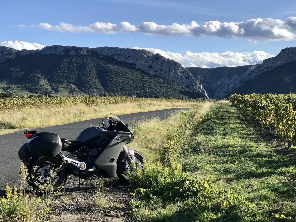 Une moto près des vignes avec la montagne au fond
