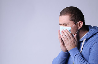 Man with mask coughing and covering his mouth with hands, on white background with copy space