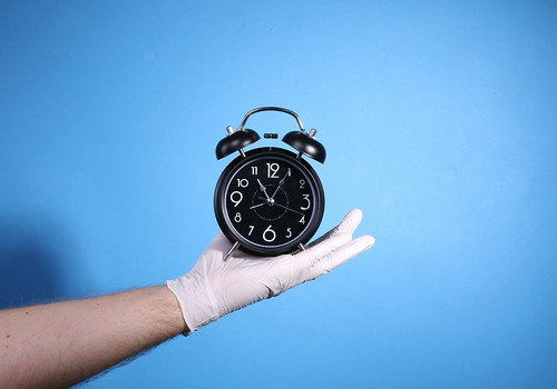 Alarm clock on the palm of a hand with surgical gloves on blue background | by focusonmore.com