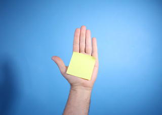 Yellow blank notepaper on palm of man's hand on blue background with copy space