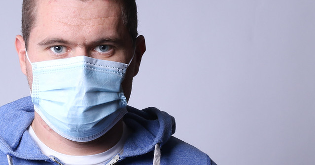 Man with surgical mask on white background with copy space