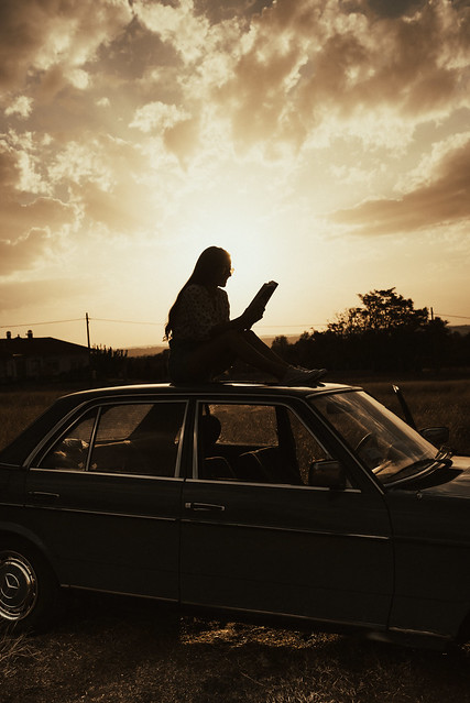 Woman sitting on a roof of a vintage car and reading a book.