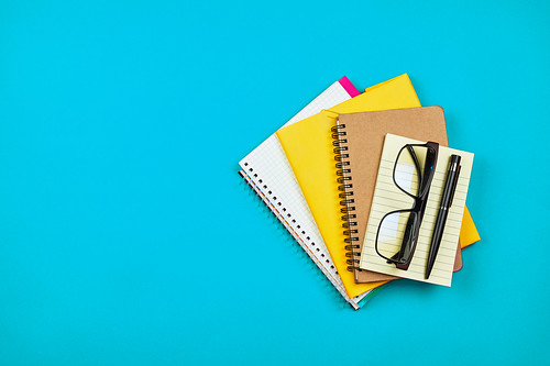 Pile of different notepads and diaries on blue background | by verchmarco