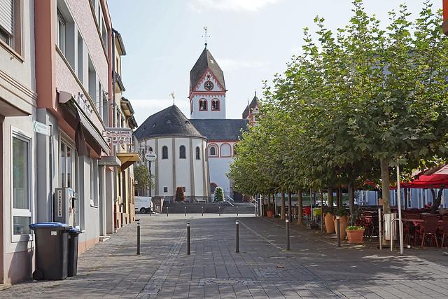 Ein Fußweg führt auf eine romanische Kirche zu, links Wohnhäuser, rechts eine baumbestandene Café-Terrasse