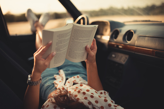 Woman lying on the front seats of a car with her legs resting on a car door and reading a book.
