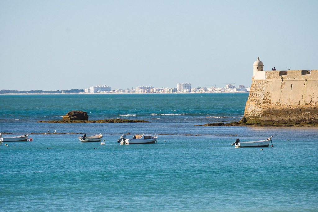 A corner of the castle surrounded by the blue waters of the ocean. There are small boats on the water. In the background some tall buildings can be seen.
