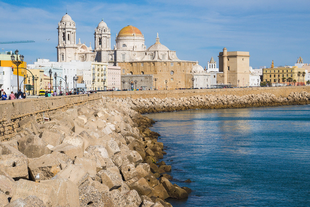One the right hand side of the photo there is the calm, blue, Atlantic Ocean. A concrete wall separates the main road and the city from the water. In the centre of the picture there is the Cathedral of Cadiz, sitting on the other side of the street from the water.