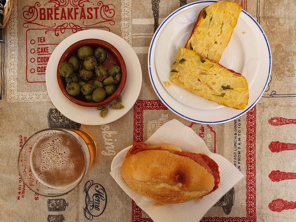 A picture taken from above of tapas: a Spanish potato omelette, a bowl of green olives and a sandwich with jamon, near a small glass of beer.