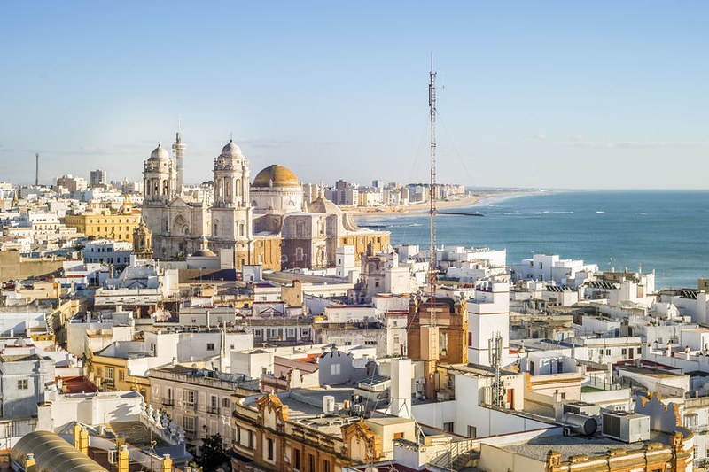 Cityscape by the Atlantic Ocean with the famous Cathedral of Cadiz, and the rooftops of the buildings around it. In the top left you can see the blue waters of the Atlantic Ocean.