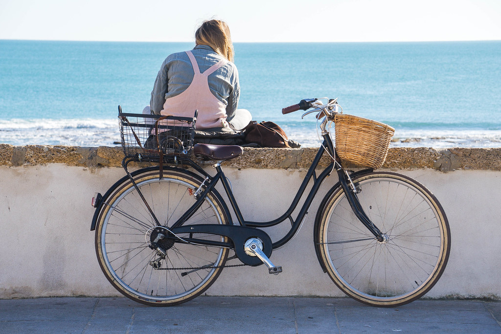 A girl sitting on the wall of the promenade, facing the sea, reading. Behind her there, in front of the picture, it's her black bike with a rattan basket in front and a wooden crate in the back. She is wearing pink overalls and a blue shirt underneath. Her blonde hair is pulled on one side of her head.