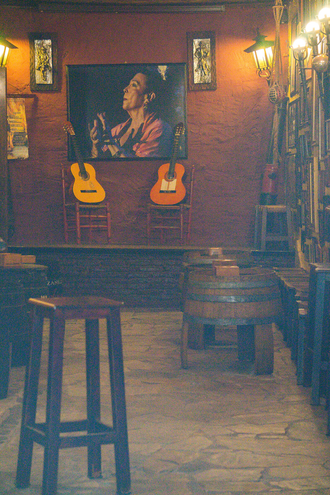 The interior of the flamenco bar, with two guitars arranged on chairs, underneath the painting of an old flamenco dancer who is clapping her hands. The interior is quite atmospheric because there isn't much light.