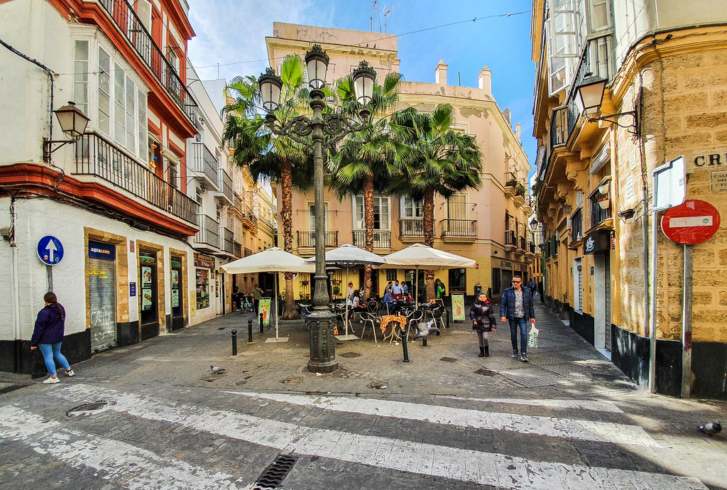 A very small square between two lanes in the old town of Cadiz. In the middle there is a small cafe with three white umbrellas underneath two palm trees.