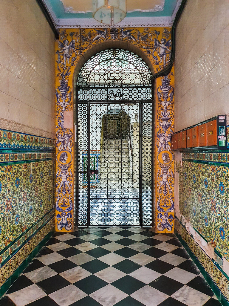 The entrance to a building in the El Populo neighborhood. The hallway is tiled with mosaic pieces representing blue and red flowers on a yellow background. Around the main gate there are paintings of baby Greek gods resembling Eros, and different Roman pots. They are painted with white and light blue on an orange background
