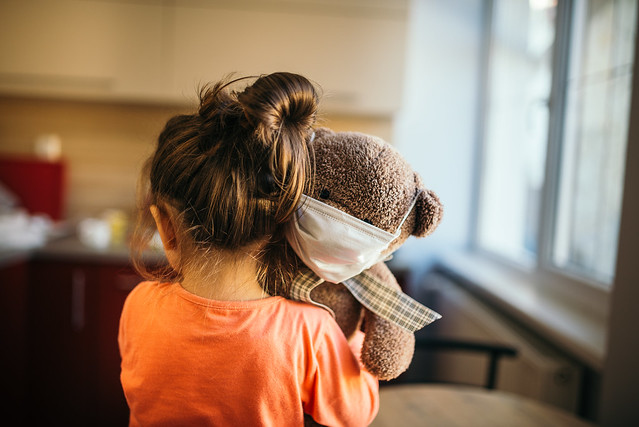 Child holding a teddy bear with medical protective mask.