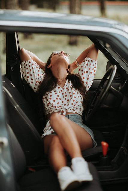 Woman sitting in a vintage car.