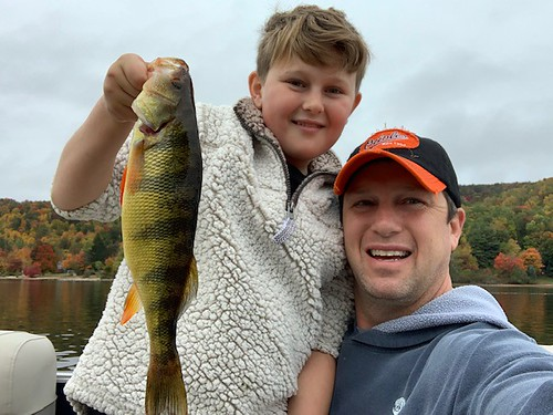 Photo of boy and father holding a yellow perch