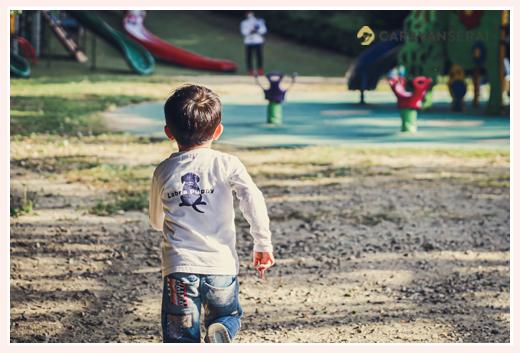公園で遊具に向かって走る男の子の後ろ姿