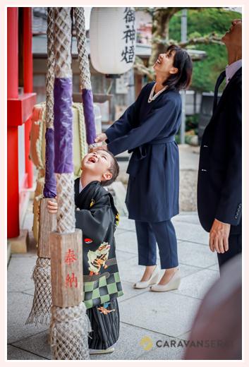 七五三 神社の拝殿前で鈴を鳴らす男の子とママ
