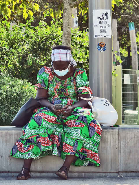 Sitting African lady consulting her mobile phone