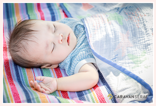 芝生に敷いたレジャーシートの上で眠る赤ちゃん