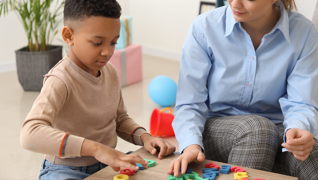 Speech and language therapist with young child.