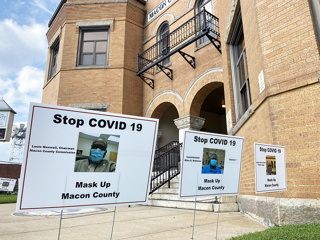 Signage showing commissioners wearing masks