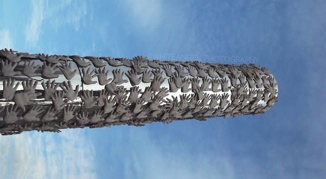 Sculpture tower of creative hands recalling the Flue chimney of the jute mills in Piazzola Sul Brenta -PD- (Piazza della Filatura, adjacent the Jute Mill Camerini)