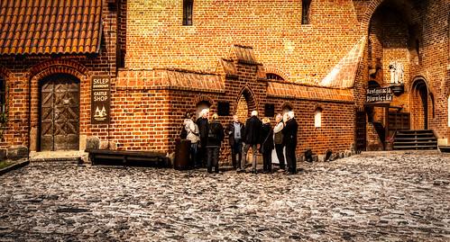 Tourists outside the Castle Shop located inside the main quad of the Malbork Castle, Malbork, Poland.  059-Edita