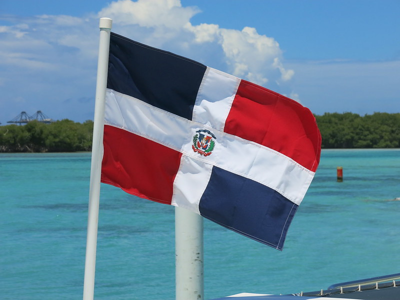Photo of Dominican Republic flag flying in front of the ocean
