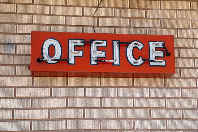 Old rustic neon sign for a motel office, taken at an abandoned, seedy motel