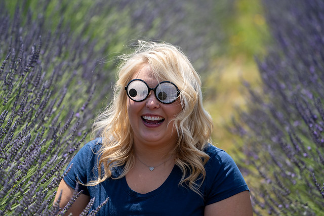 Crazy Blonde woman wearing googly eyes novelty sunglasses while sitting in a field of lavender, looking to left