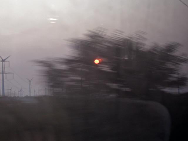 Eine aufgehende orangefarbene Sonne hinter von der Geschwindigkeit des Zuges verwischten Sträuchern