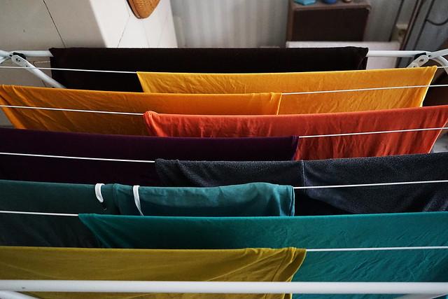 Verschiedenfarbige T-Shirts hängen nach Farben sortiert auf einem Klapp-Wäscheständer