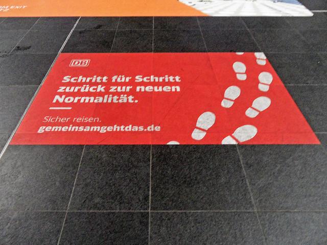 """Aufkleber der Deutschen Bahn mit dem Text """"Schritt für Schritt zurück zur neuen Normalität. Sicher reisen. gemeinsamgehtdas.de"""""""
