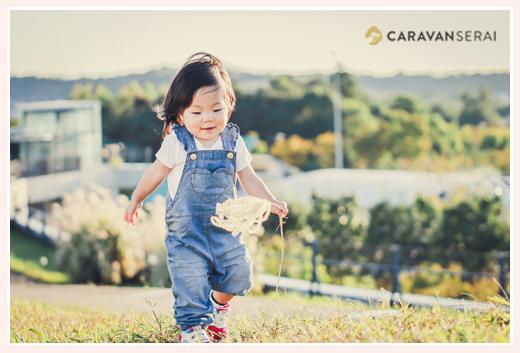 ススキを手に歩く女の子 服装はオーバーオール