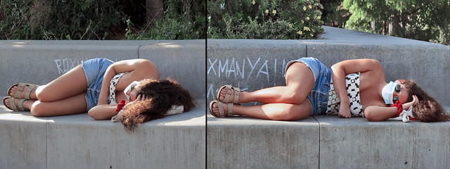 Pretty girl taking a nap lying on the seats of the Mandela Gardens in accordance with coronavirus precautions