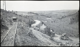 Steam driven crushing plant at bottom end of railway tracks on hillside. Tip carts on road below crusher-Used in the History of Main Roads book | by Queensland State Archives