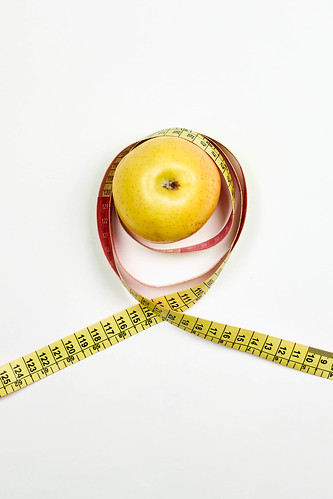 Apple and measuring tape on white. Dieting and healthy lifestyle concept | by wuestenigel