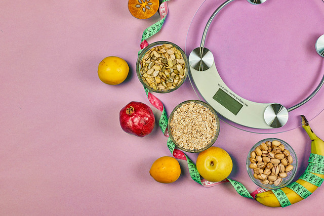 Healthy nutrition. Scales, fruits and nuts on pink background