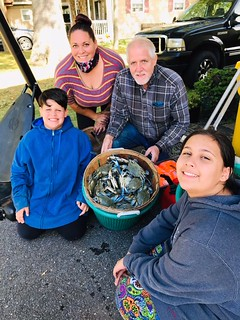 Photo of family with a basket of blue crabs