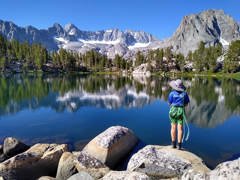 Cell phone camera photo of Vicki posing at Summit Lake with the Palisade Glacier in the distance