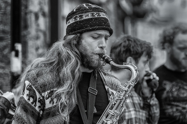 Sax player busking with his friends