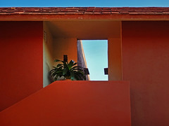 Orange walls with a cut-out framing the blue sky in Huatulco, Mexico