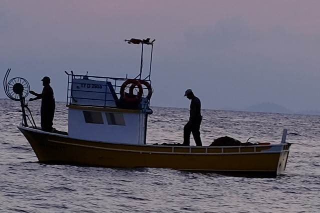 Şafak vakti balıkçı ağları toplanıyor.