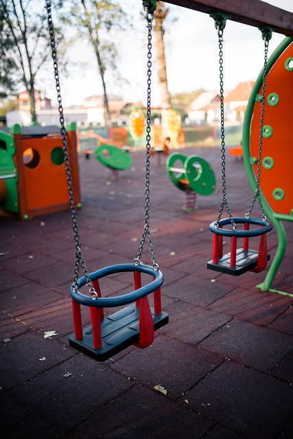 Set of colorful chain swings on modern kids playground.