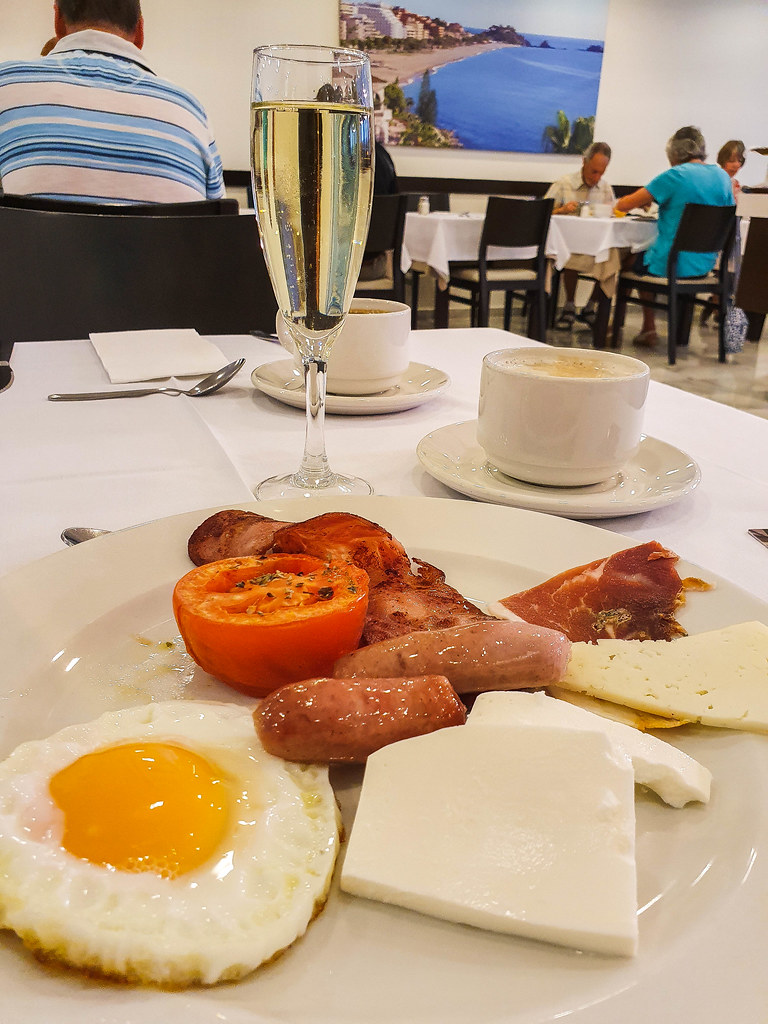 A plate with a poached egg with a perfect yellow yolk, two small sausages, a red tomato with green herbs on top, two white slices of fresh cheese, a slice of jamon iberico and a slice of aged manchego cheese. On the table there are also two white cups of coffee and a flute glass filled with cava.