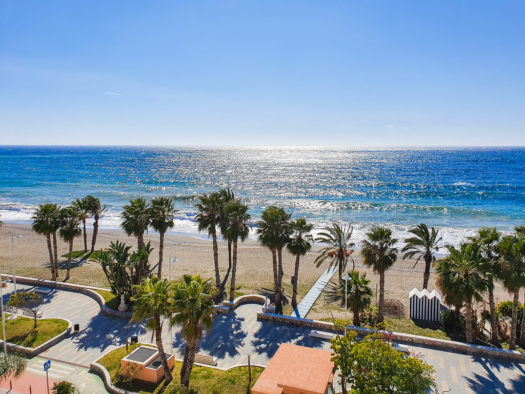 The view in front of the hotel Hotelios: the promenade lined up with palm trees, the sandy beach beyond it, and the sea in the far end of the photo. The sea is blue and it appears like its sparkling because of the rays on sun landing on it.